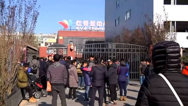 People stand in front of the main gate of the RYB New World Kindergarten in Beijing's Chaoyang district.