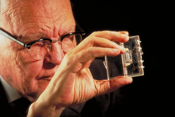 Late in his life, Jack Kilby holds his first integrated circuit, which is encased in plastic. Photo via Texas Instruments, via Earth & Sky