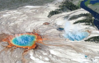 An aerial flight over Yellowstone's Midway Geyser Basin in 2004 shows Grand Prismatic Spring and Excelsior Geyser Crater, which drain into the nearby Firehole River.  Image via USGS