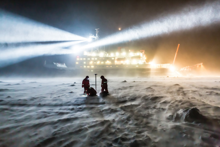 Scientists on sea ice under dark sky, with a huge ship behind them with multiple searchlights.