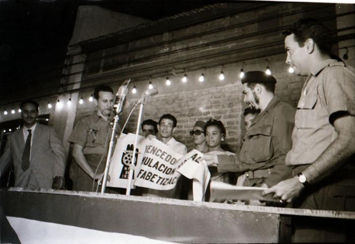 Comandante Ernesto Che Guevara, minister of Industries, presents the National Literacy Campaign banner to paint factory workers.