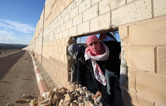 Palestinian-youths-appear-through-a-hole-they-dug-in-the-controversial-Israeli-separation-wall-in-the