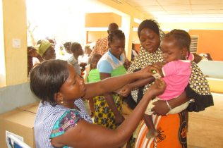 Measuring of mid-upper arm circumference of a child during a community outing organized by Ouagadougou CRNE