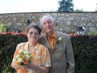 Photo of a senior couple, lady with glasses on the left with a pink and white checkered blouse holding a bouquet of flowers and a gentlemen in a grey suit on the right.