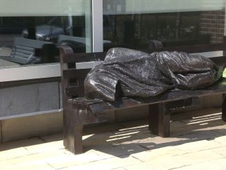 Photo of Statue of Christ the Homeless on a bench in Toronto
