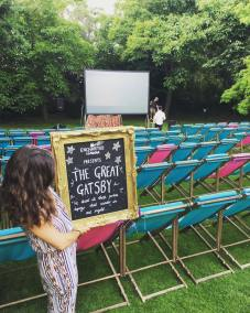 Ellen holding out gold-framed sign tonight. Enchanted Cinema set-up almost ready for show time. Roll on The Great Gatsby under the stars