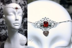 A deep red gem is flanked by glass crystals atop a filigree base. A single heart dangles from the front.