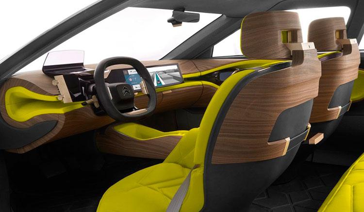 Imagen interior del Citroën CXperience, donde podemos apreciar la madera y las telas de su habitáculo, junto a su pantalla de 19 pulgadas superpanoramica.