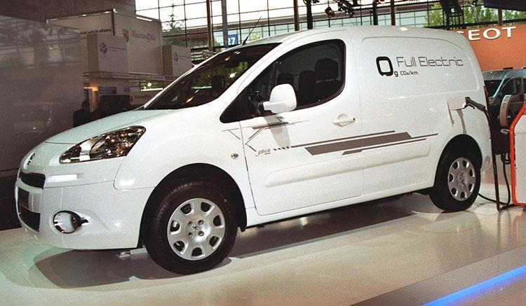 Imagen donde vemos una Peugeot Partner Electric en exposición, conectada a un punto de recarga, que conecta por el lateral de la furgoneta.