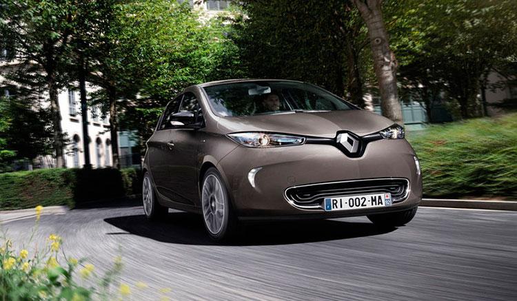 Imagen frontal de un Renault ZOE ZE 40 de color gris titanio circulando por ciudad.