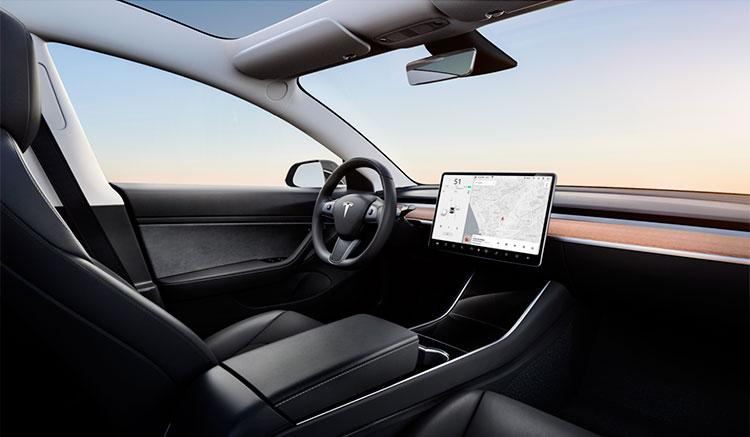 Imagen donde podemos ver el interior del Tesla Model 3, con techo solar y un panel de mandos centrado en la pantalla central y el volante.