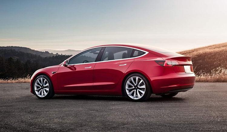 Imagen lateral-trasera de un Tesla Model 3 de color rojo.