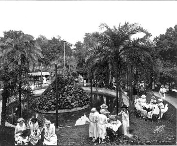 """A tea party in """"Plant Park"""", which was an attraction of the Gilded Age Tampa Bay Hotel. The park and building still exist as part of the University of Tampa. There was a small zoo in the park, which may explain the posts (fence?) around the pond."""