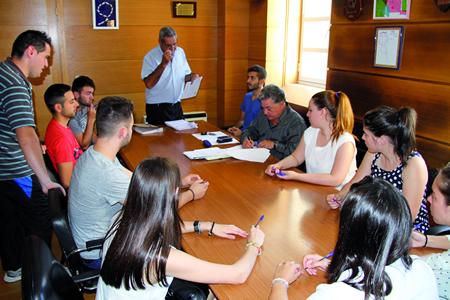 O alcalde de Quiroga, Julio Álvarez, durante a sinatura dos contratos do Plan de Emprego Xuvenil na Casa do Concello, xunto cos mozos que se incorporaron ó seu posto de traballo para os meses de verán. (Foto cedida).