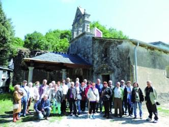 Foto de familia do grupo de asociados de Lugopatrimonio diante da igrexa de San Mamede, na parroquia de Vilasouto, no Incio, acompañados do vicepresidente da Deputación, Antonio Veiga, e varios veciños. (Foto cedida).
