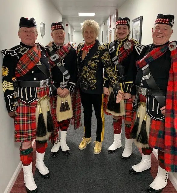 The bagpipers pose with Sir Rod