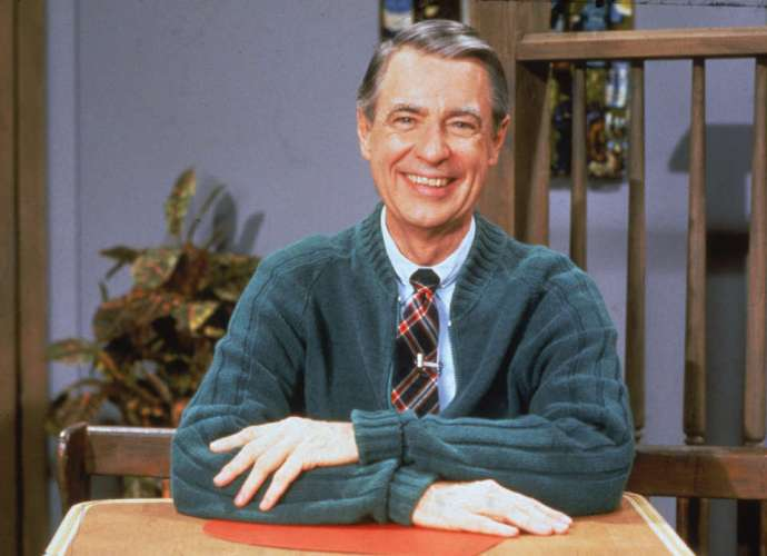 A picture of Mr Rogers wearing a green cardigan and smiling at the camera