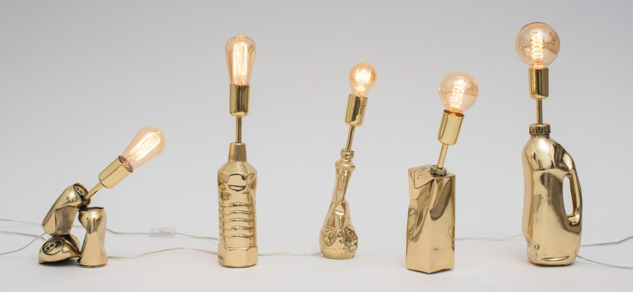 Five golden coloured lamp stands made out of recyclable material