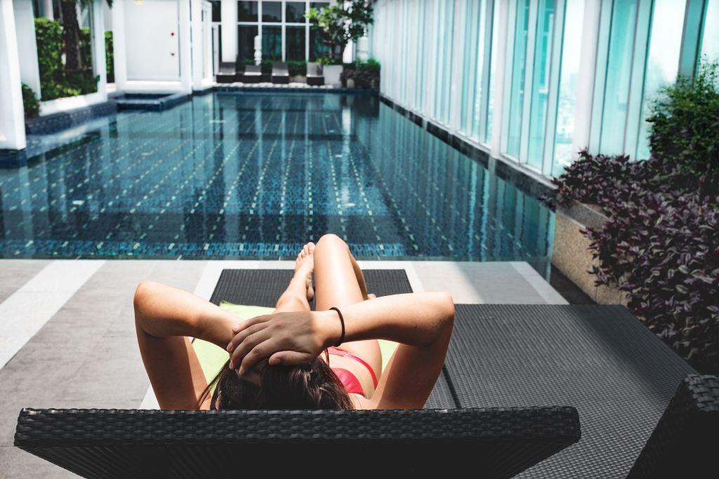 Femme au bord d'une piscine d'interieur