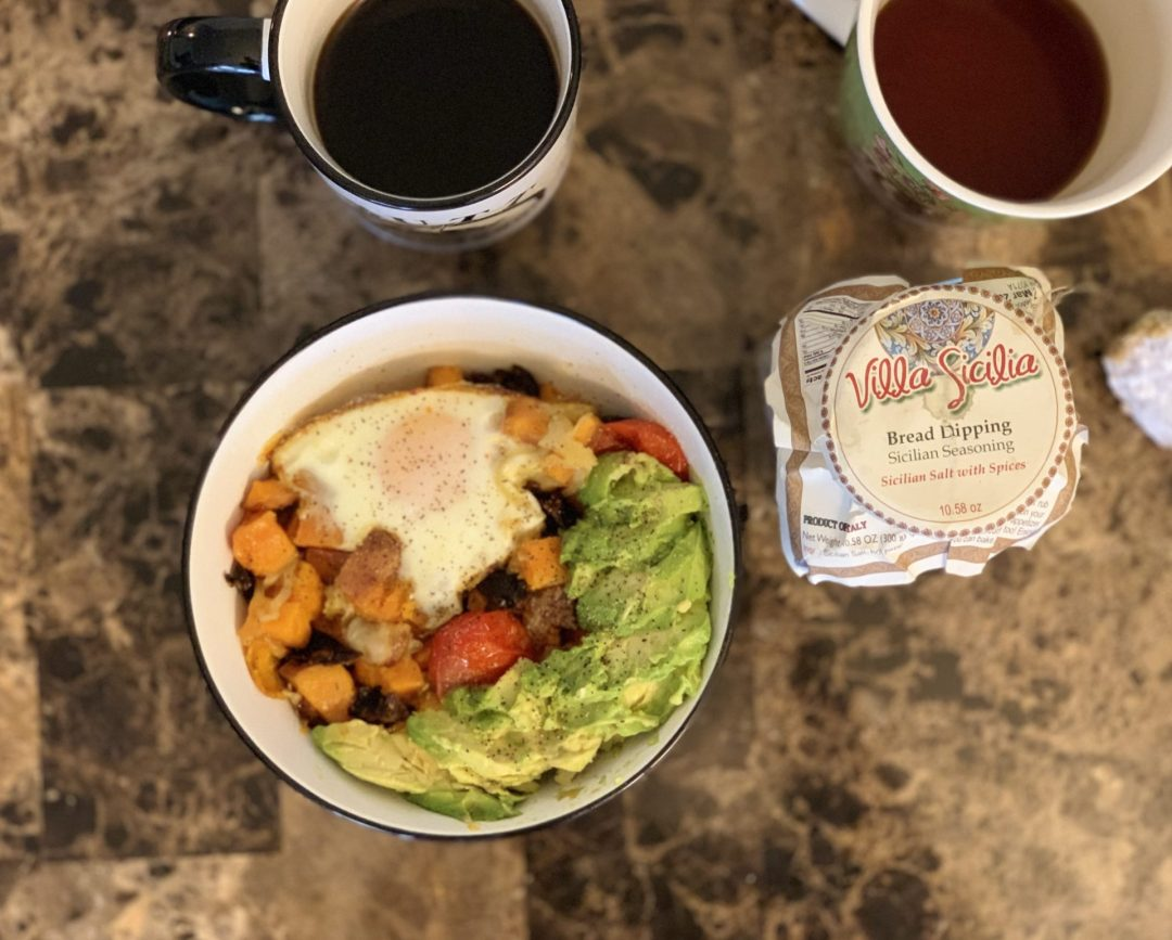 Sweet potato hash featuring baked eggs, caramelized onions, roasted tomatoes, , roasted garlic, chopped sun-dried tomatoes, topped with mashed avocado. Sicilian Salt with Spices. Two cups of coffee.