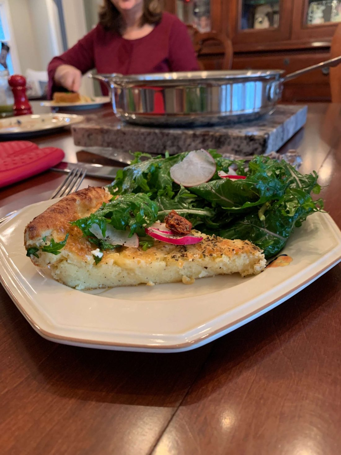 A slice of Savory Dutch Baby Pancake with Arugula, mozzarella, parmesan, sun-dried tomatoes, and radishes for brunch