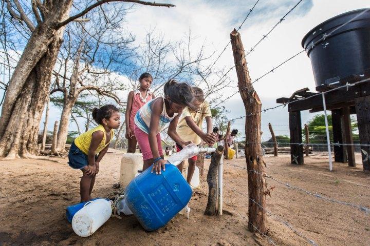 """Los niños y la """"llave"""" de agua en el desierto; comunidad de Jawapiakat; Maicao, Guajira. Hanz Rippe Gabriel"""