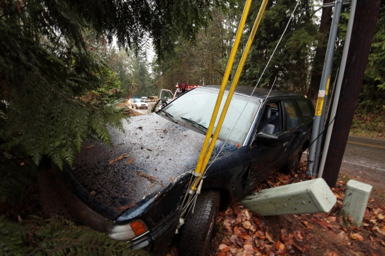 """A car that skidded off the road into a power pole is winched away by a tow-truck while the sheriff holds up traffic. Note: the young, inexperienced, extremely lucky driver was unharmed."""