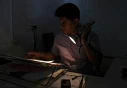 An officer reads documents with the help of a torch at the driving registration and license authority office during a power-cut in Chandigarh