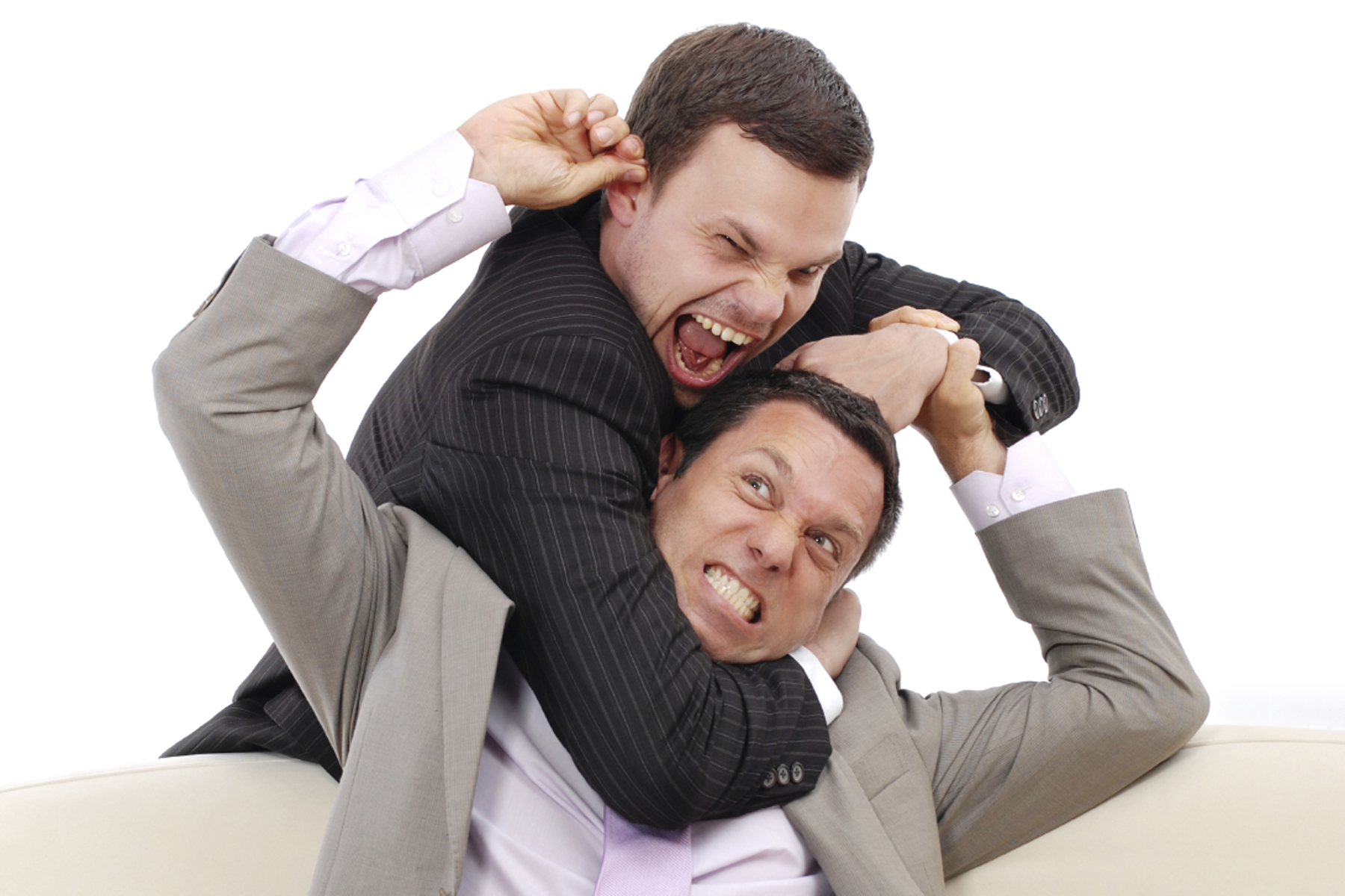Two businessmen fighting on a couch in front of a laptop