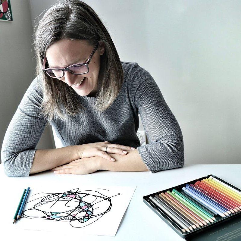 Junge Frau betrachtet lächelnd ein NEURODINGS. Neurokreatives Zeichnen geht spielerisch leicht und du hast Freude an deinem Bild. NEURODINGS Workshops für dich