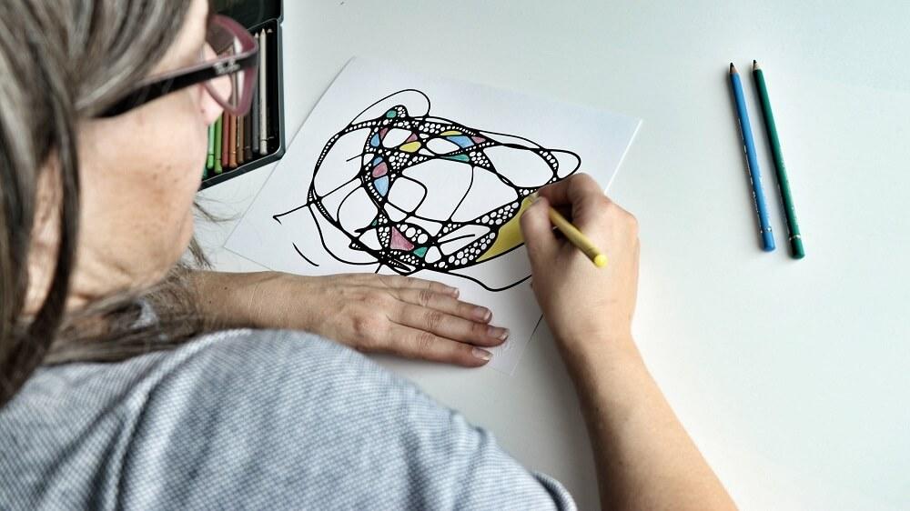 Junge Frau zeichnet ein NEURODINGS und wird dabei über die Schulter fotografiert. Bild als Dekorationsobjekt für das NEURODINGS Freebie