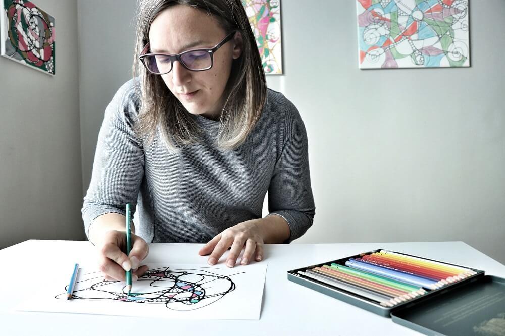Junge Frau zeichnet an einem Tisch ein Neurodings®. Beispielbild für neurokreatives Zeichnen