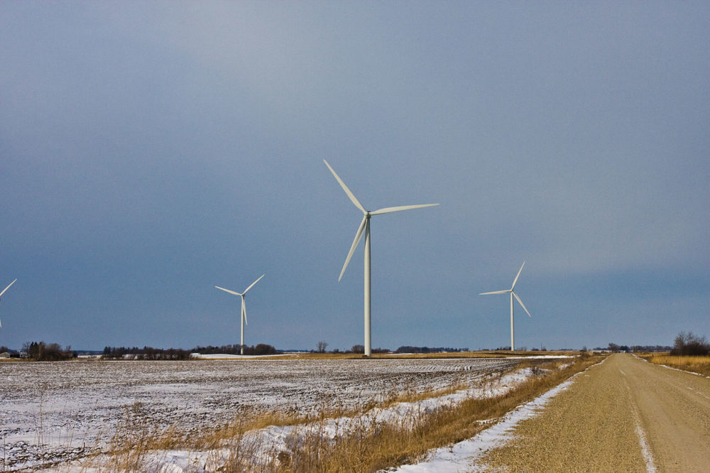 three wind turbines amid a snowy Iowa landscape