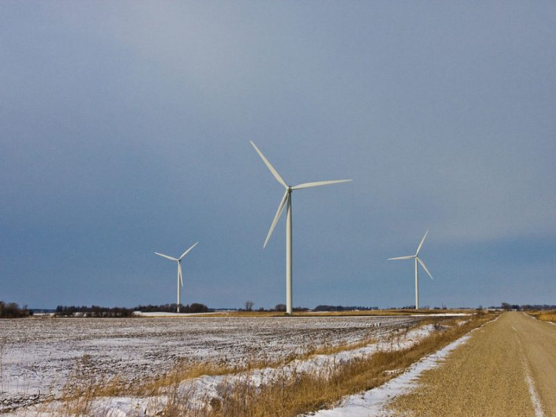 three wind turbines amid a snowy Iowa landscape