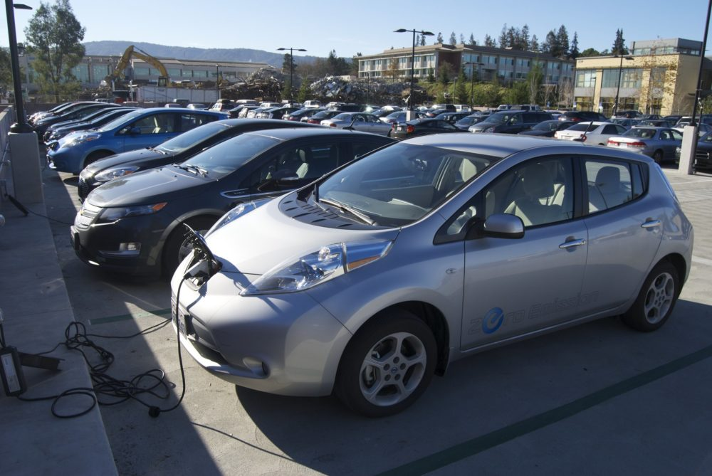A row of electric and hybrid vehicles gather at a charging station.