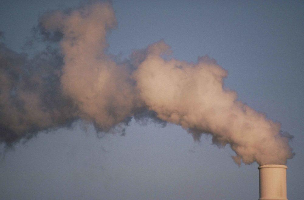 clouds of smoke rise from a smokestack
