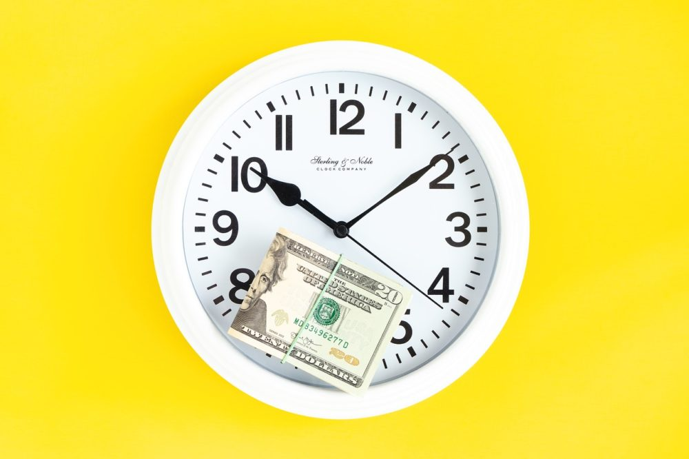 a bundle of $20 bills rests atop a white clock on a yellow background