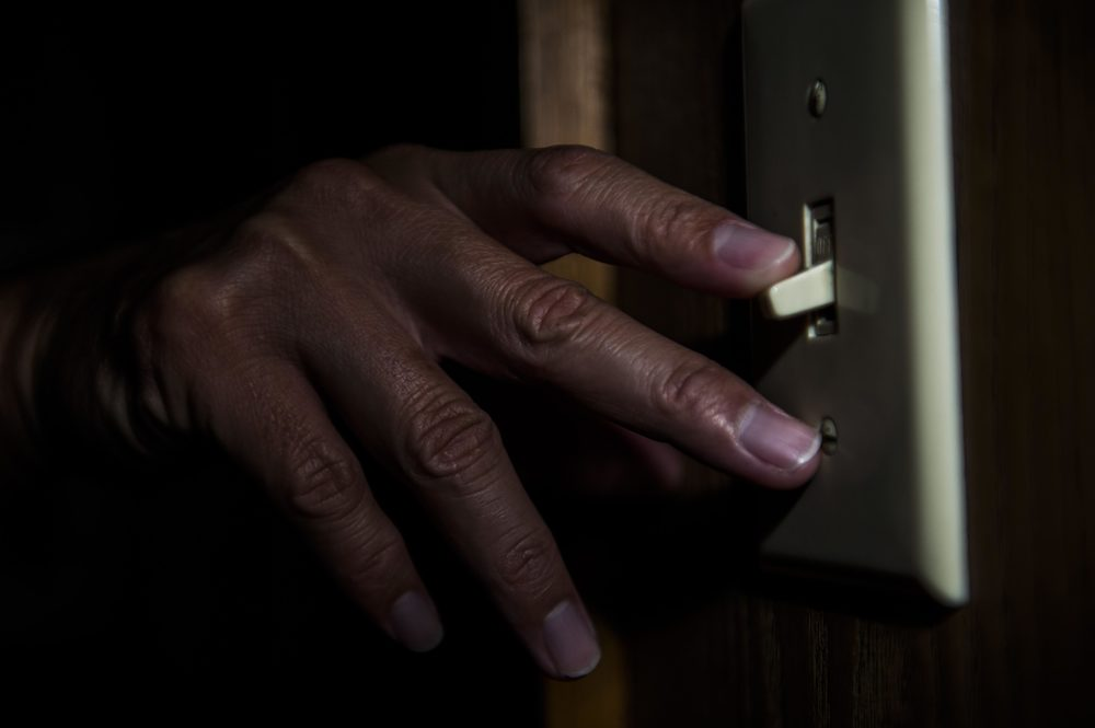 a hand flips a light switch