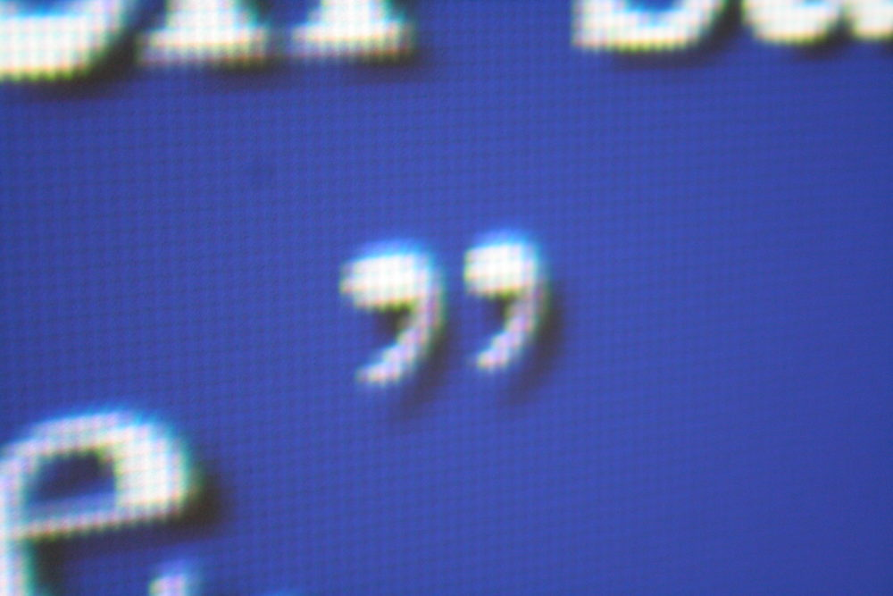 a white pixelated close quotation mark on a blue digital backgrouns