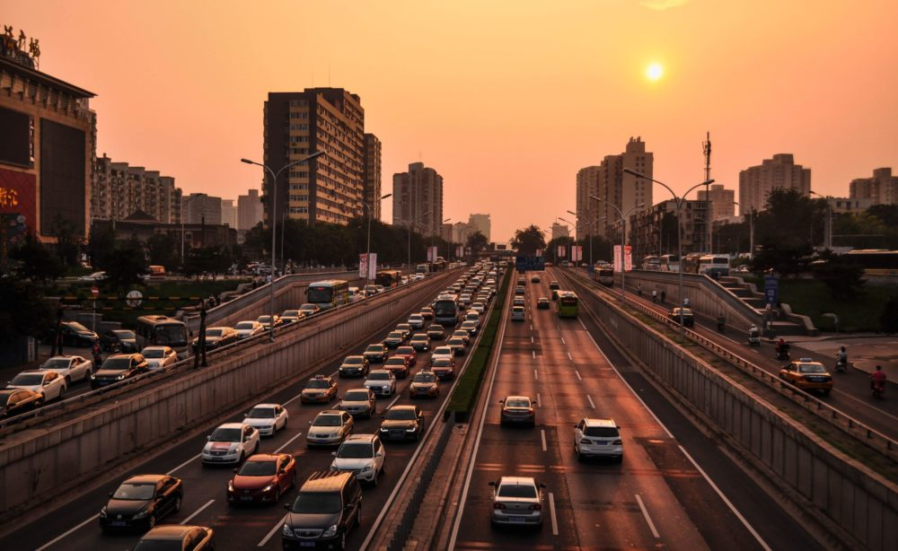 A hazy orange sky reflects a golden light on a six-lane roadway filled with personal vehicles.