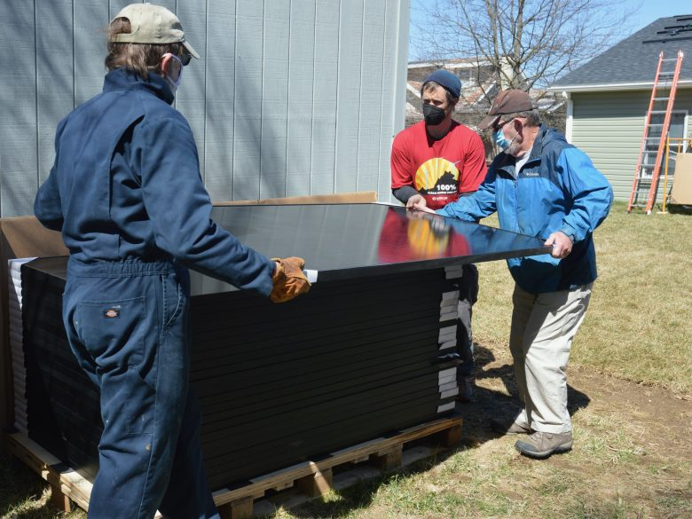 A group of three workers lift a solar panel from a waist-high stack.