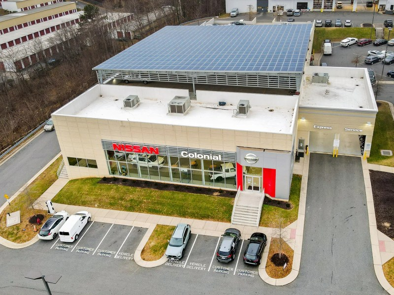 Aerial photo of a car dealership whose roof is nearly completely covered in solar panels.
