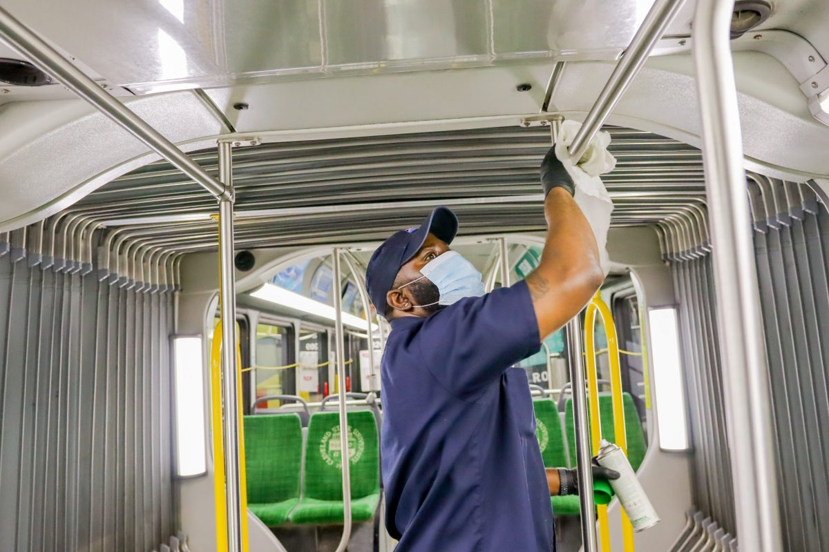 A masked worker uses a rag to clean a handrail inside a public bus.