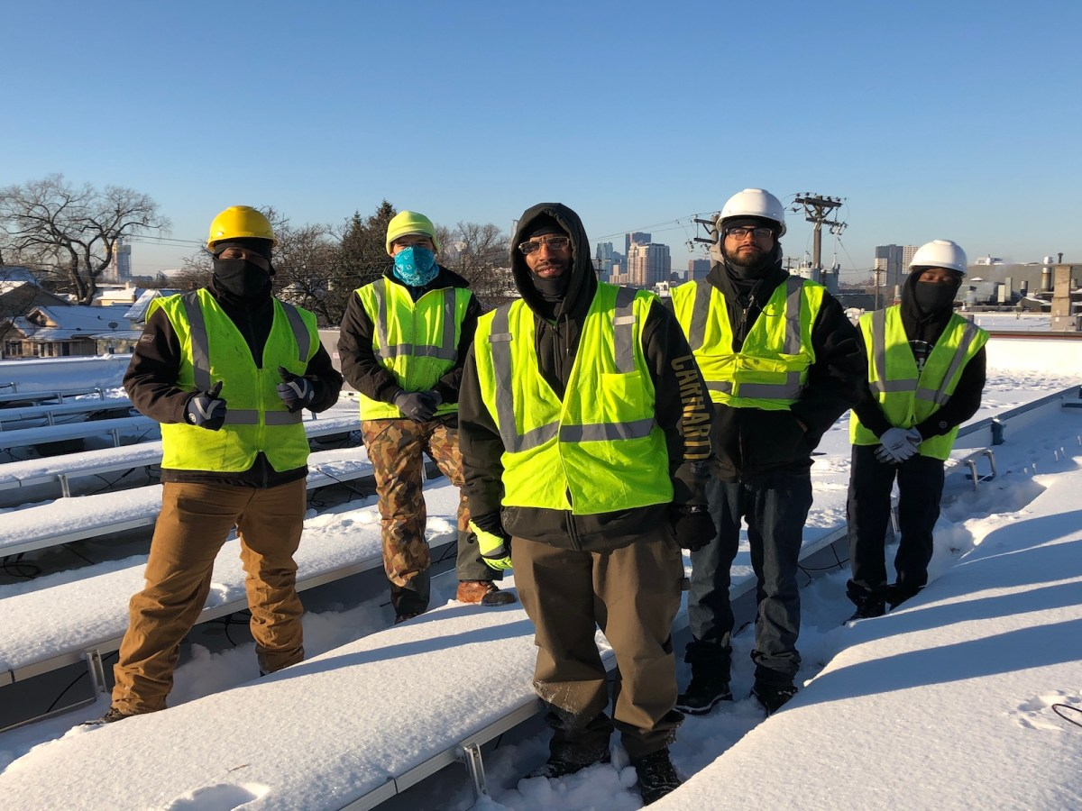A group of people in reflective vests stand on a roof surrounded by snow-covered solar panels.