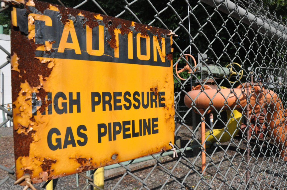 """A rusted sign on a chain link fence reads """"caution, high press gas pipeline"""""""