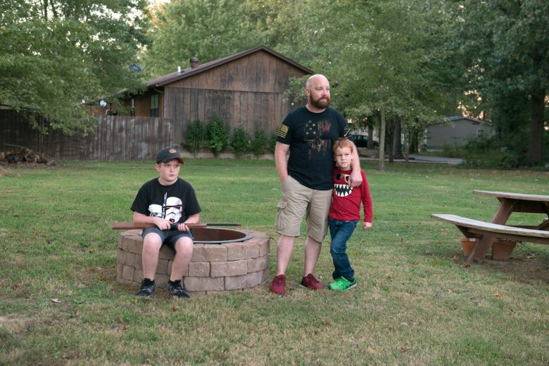 Brad Campbell with his sons in his backyard in Herrin, Illinois in October 2018. Luke, then 6, stands next to his father, and Nate, then 11, sits on the fire pit his grandfather Glen Campbell enjoyed sitting by.