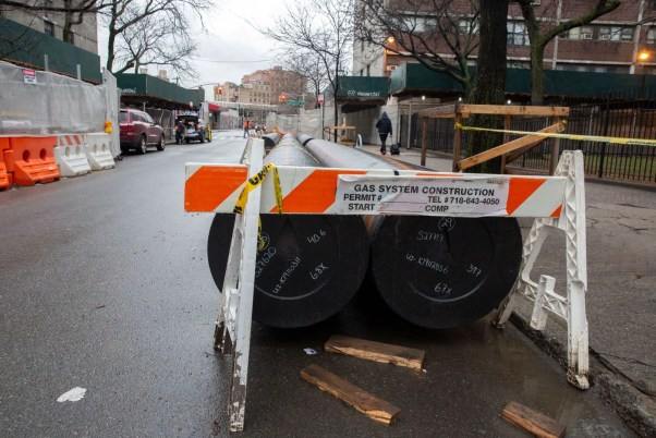 Pieces of pipe sit on a Brooklyn street under a road closed sign