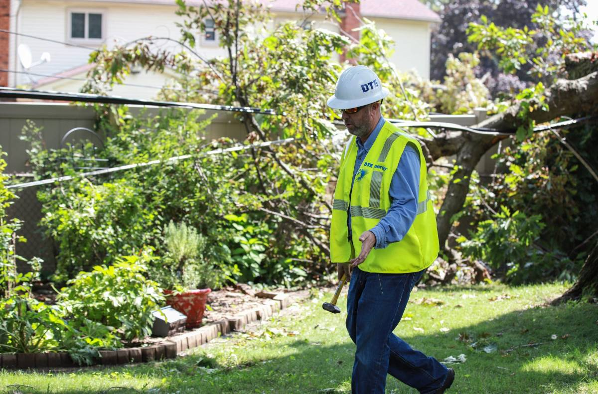 A DTE employee cautions off a section of a backyard after a tree fell, hitting wires, in Dearborn Heights in August.
