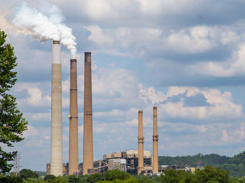 The Conesville, Ohio coal power plant features three large smokestacks set against a blue sky.