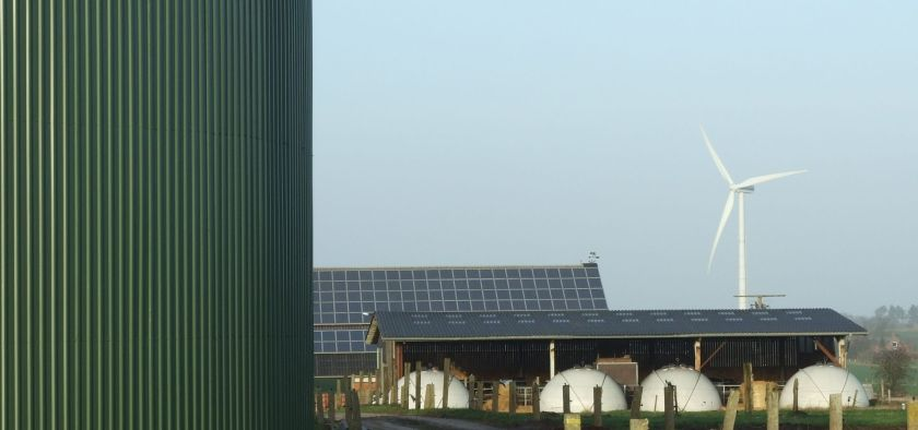 view of a farm with biogas, solar panels on the roof and a windmill in the background